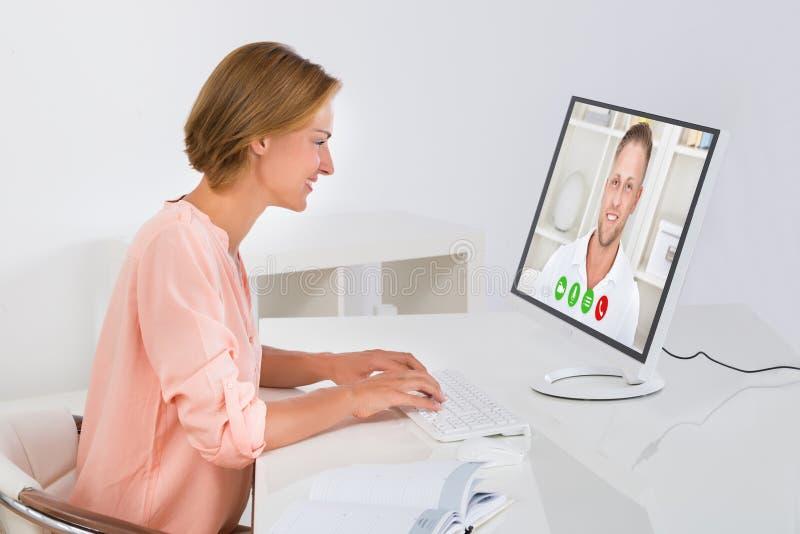 Mulher Videochatting no computador imagens de stock