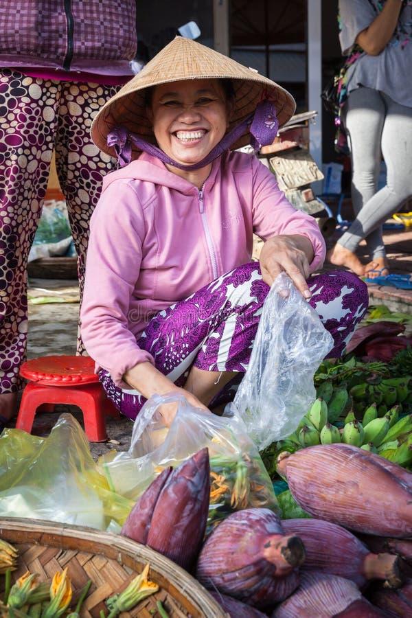 Mulher vietnamiana de sorriso no chapéu tradicional que vende frutos no mercado de rua, Nha Trang, Vietname fotografia de stock royalty free
