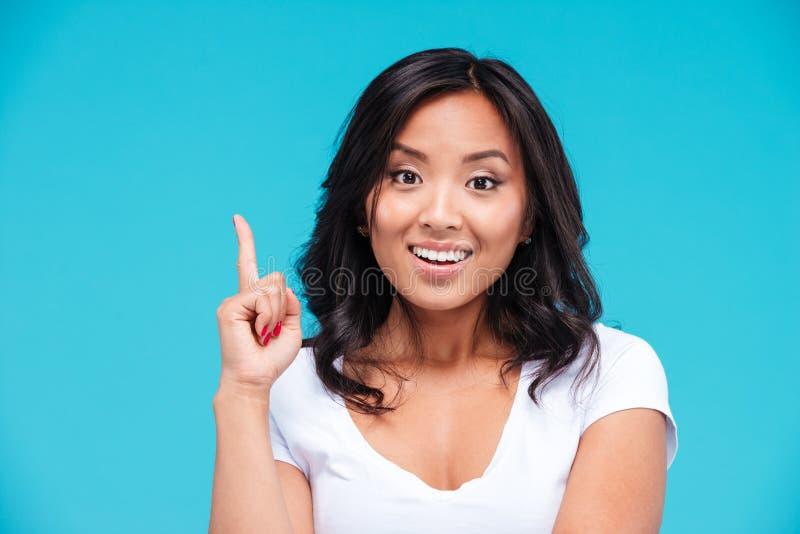 Mulher vietnamiana inspirada feliz que aponta acima e que tem uma ideia imagens de stock royalty free