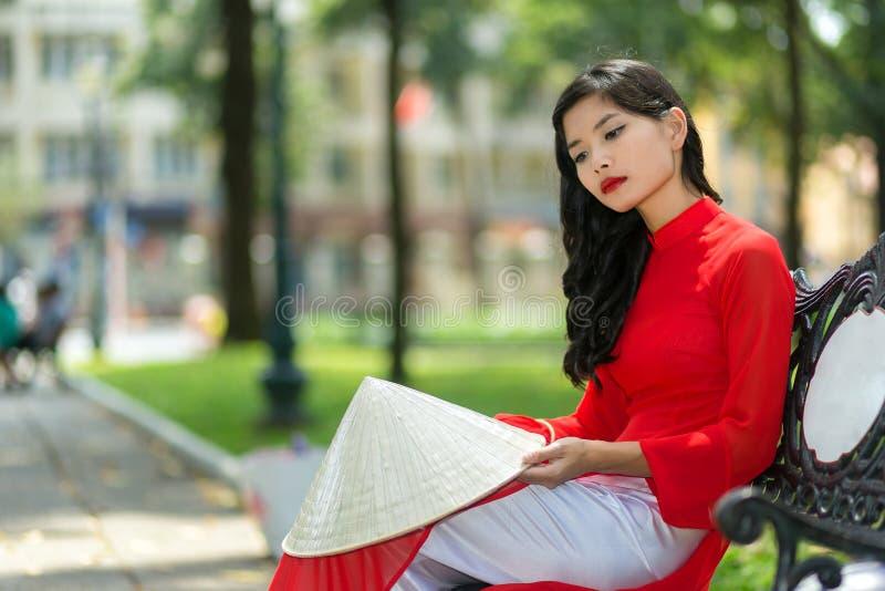 Mulher vietnamiana nova triste que senta-se em um banco imagem de stock royalty free