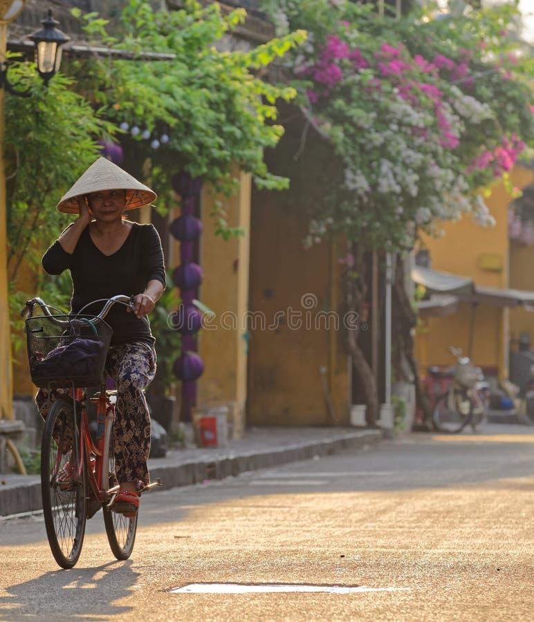 Mulher vietnamiana que bicycling em Hoi An fotos de stock