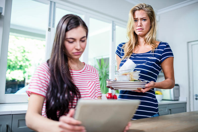 Mulher virada que mostra pratos sujos ao amigo fotografia de stock royalty free