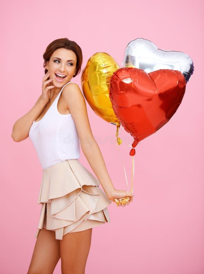 Mulher Vivacious com os balões dados forma coração fotografia de stock