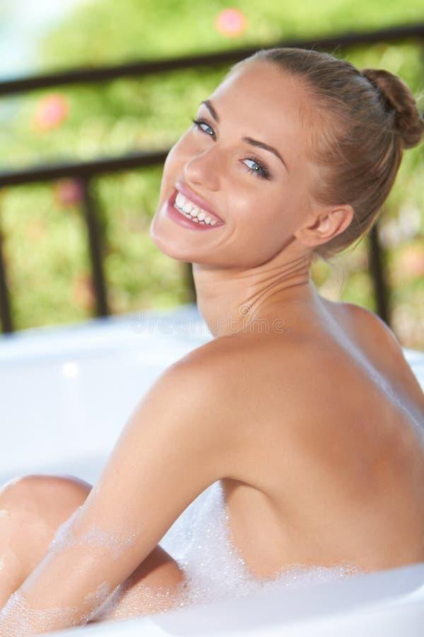Mulher Vivacious que aprecia um banho de bolha imagens de stock