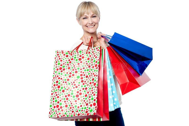 Mulher Vivacious que guardara sacos de compras coloridos imagens de stock royalty free