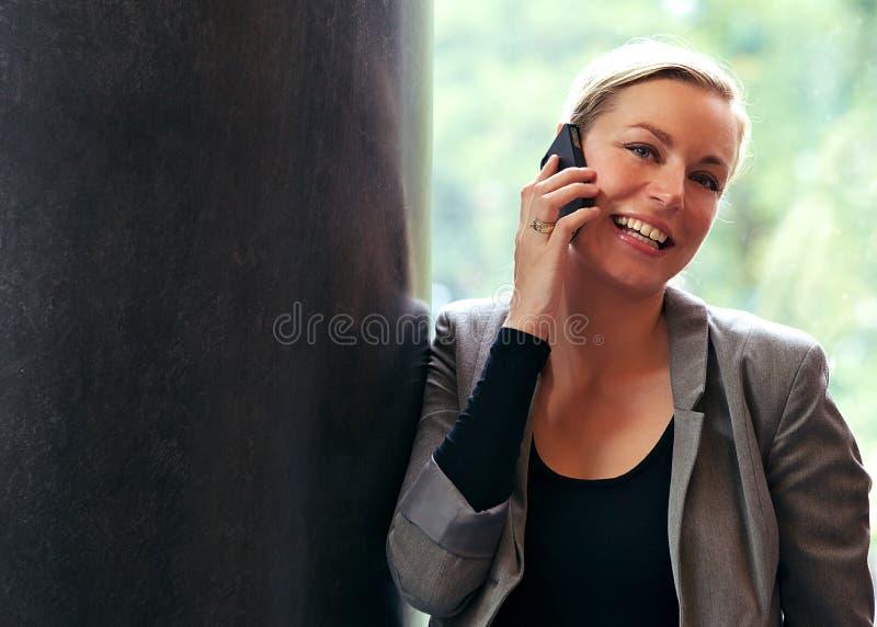 Mulher Vivacious que usa um móbil foto de stock