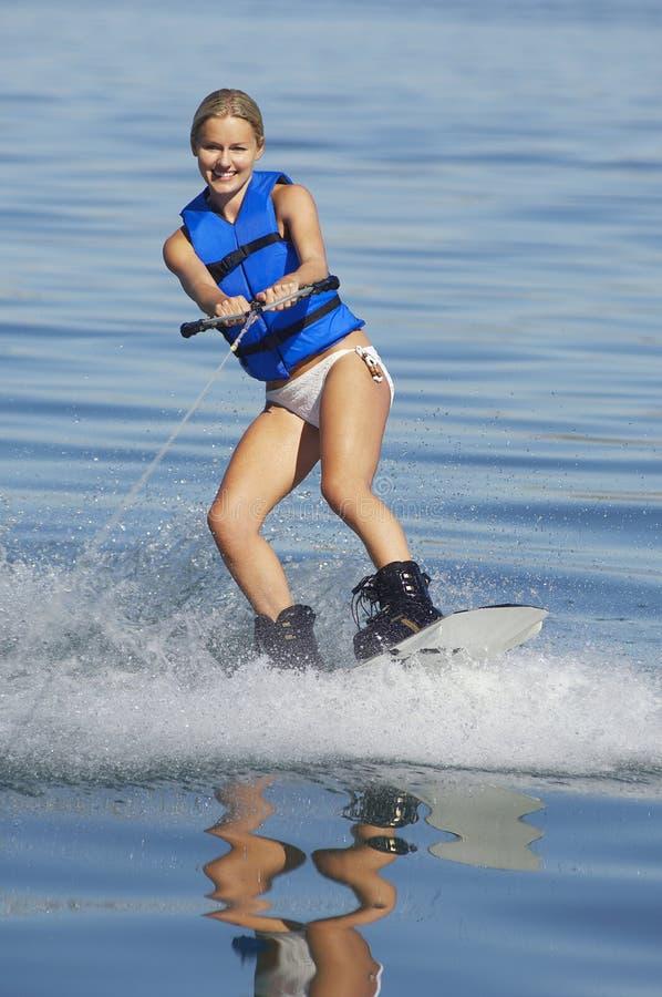 Mulher Wakeboarding no lago imagem de stock
