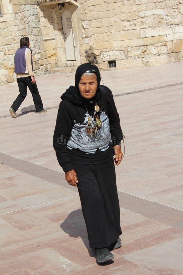 Mulheres adultas na roupa preta com o papagaio na cabeça no passeio das palmeiras, praia de Finikoudes, Larnaca, Chipre fotografia de stock royalty free
