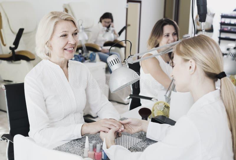 Mulheres adultas que fazem o tratamento de mãos foto de stock
