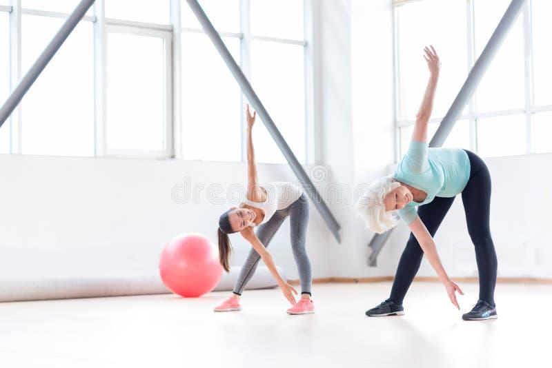 Mulheres alegres ativas que exercitam em um clube de aptidão foto de stock royalty free