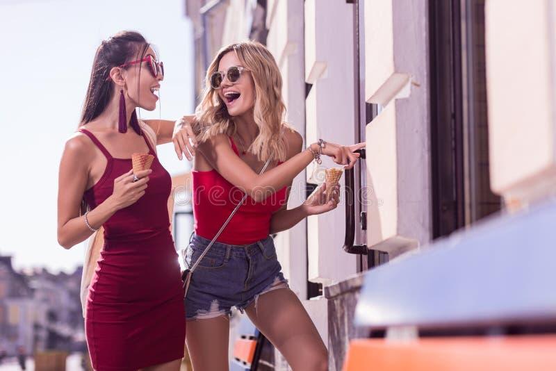 Mulheres alegres felizes que discutem o artigo da janela da loja imagem de stock royalty free