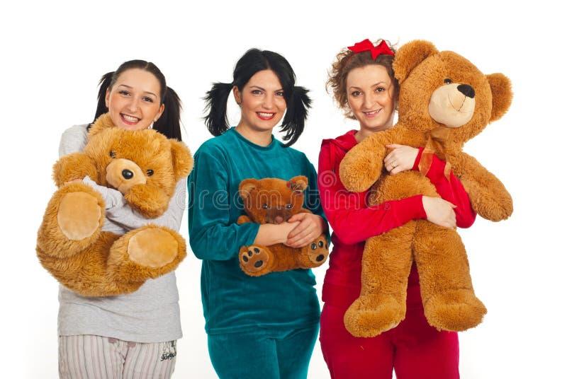 Mulheres alegres nos pyjamas com ursos de peluche fotos de stock