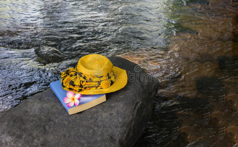 Mulheres amarelas chapéu e livro na rocha na cachoeira imagens de stock royalty free
