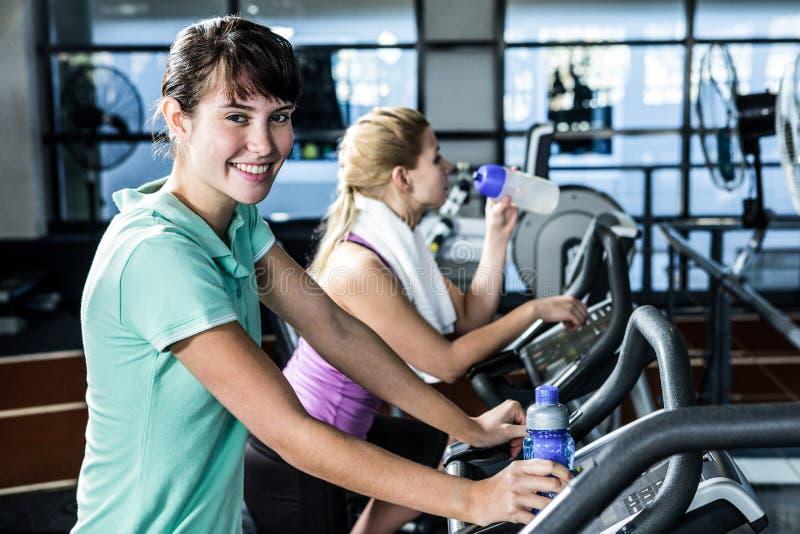 Mulheres aptas com a garrafa da água usando a bicicleta imagem de stock royalty free