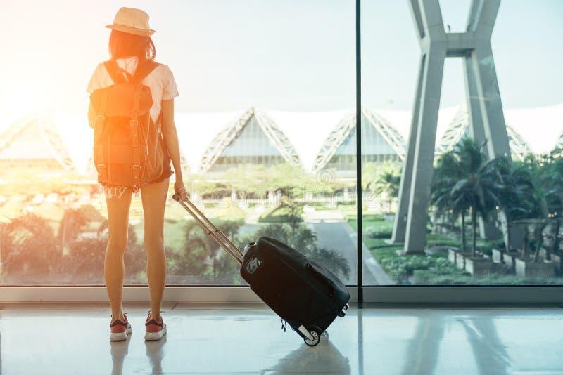 Mulheres asiáticas adolescentes que estão com bagagem ou mala de viagem na janela fotos de stock royalty free