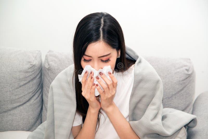 Mulheres asiáticas com esforço que sofrem das alergias e fecham o nariz com lenço de papel Devido a ter espirrar todo o tempo imagens de stock