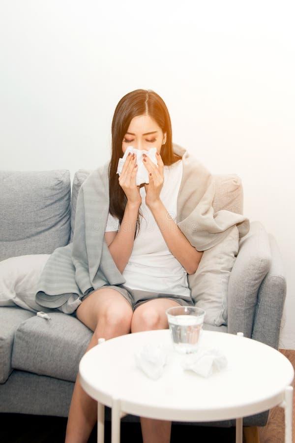Mulheres asiáticas com esforço que sofrem das alergias e fecham o nariz com lenço de papel Devido a ter espirrar todo o tempo fotografia de stock