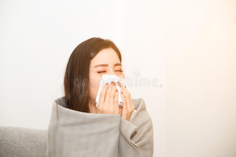 Mulheres asiáticas com esforço que sofrem das alergias e fecham o nariz com lenço de papel Devido a ter espirrar todo o tempo imagem de stock royalty free