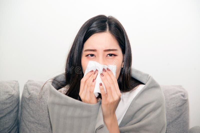 Mulheres asiáticas com esforço que sofrem das alergias e fecham o nariz com lenço de papel Devido a ter espirrar todo o tempo fotografia de stock royalty free