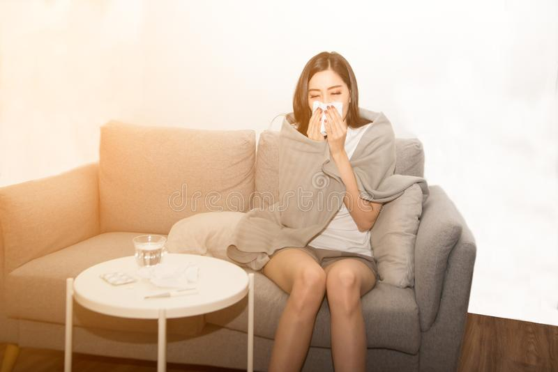 Mulheres asiáticas com esforço que sofrem das alergias e fecham o nariz com lenço de papel Devido a ter espirrar todo o tempo imagem de stock