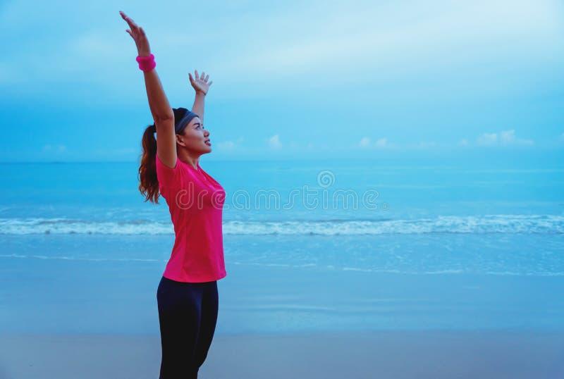 Mulheres asiáticas correndo correndo correndo na praia pela manhã amplie o relaxamento dos braços fotos de stock royalty free