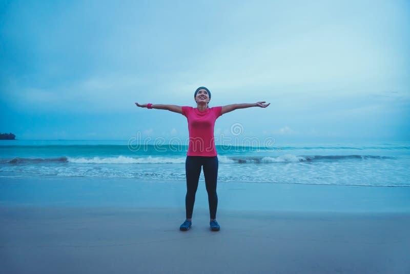 Mulheres asiáticas correndo correndo correndo na praia pela manhã amplie o relaxamento dos braços imagens de stock