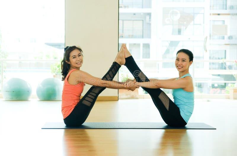 Mulheres asiáticas e ioga praticando do homem, aptidão que estica a pose da flexibilidade, dando certo, estilo de vida saudável,  imagem de stock royalty free