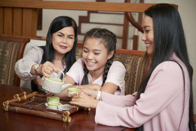 Mulheres asiáticas felizes das gerações diferentes que comem o chá foto de stock royalty free