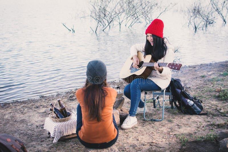 Mulheres asiáticas felizes que jogam a guitarra na estação do inverno da natureza imagens de stock