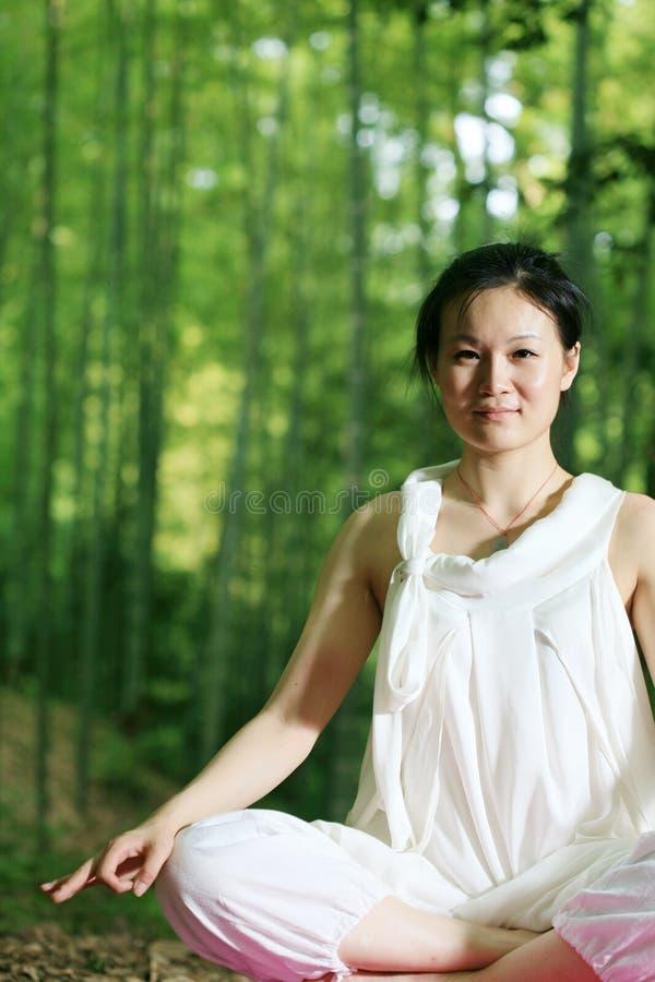 Mulheres asiáticas novas que fazem a IOGA fotos de stock royalty free