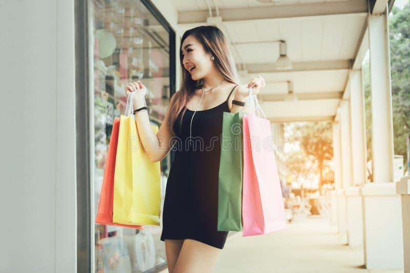 Mulheres asiáticas novas que guardam o saco de compras no shopping imagens de stock royalty free
