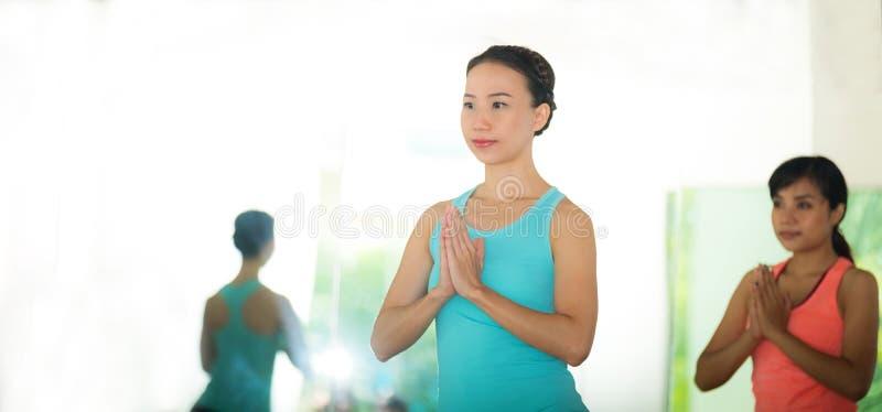 Mulheres asiáticas novas que praticam a meditação da ioga, estilo de vida saudável, foto de stock
