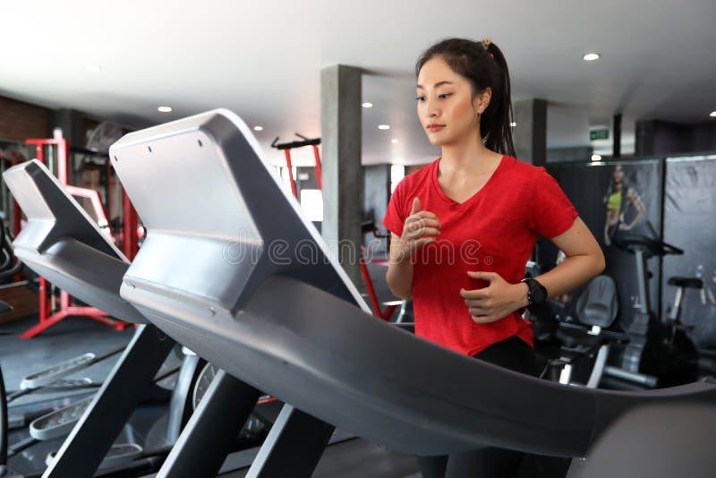 Mulheres asiáticas que correm sapatas do esporte no gym quando um caucasi novo fotografia de stock