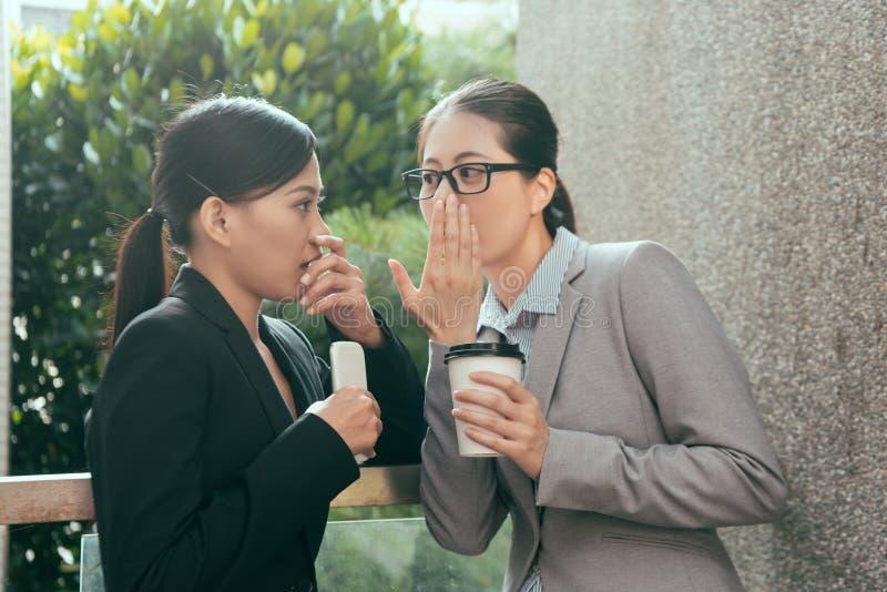 Mulheres asiáticas que falam sobre a bisbolhetice do escritório imagem de stock