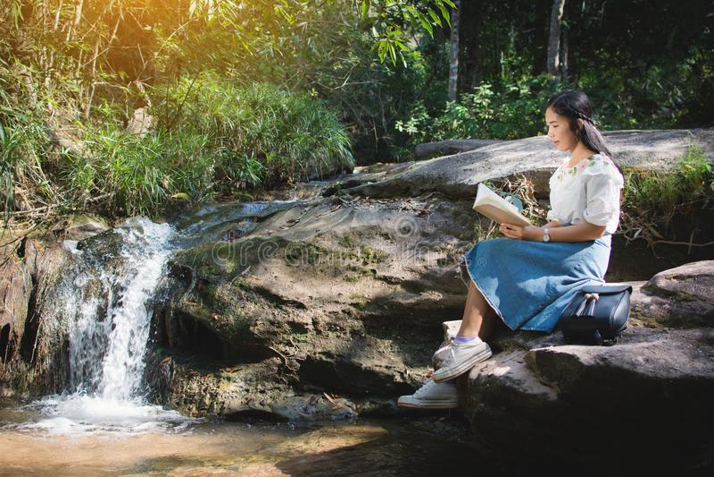 Mulheres asiáticas que leem um livro que senta-se na rocha perto da cachoeira no fundo da floresta fotografia de stock royalty free