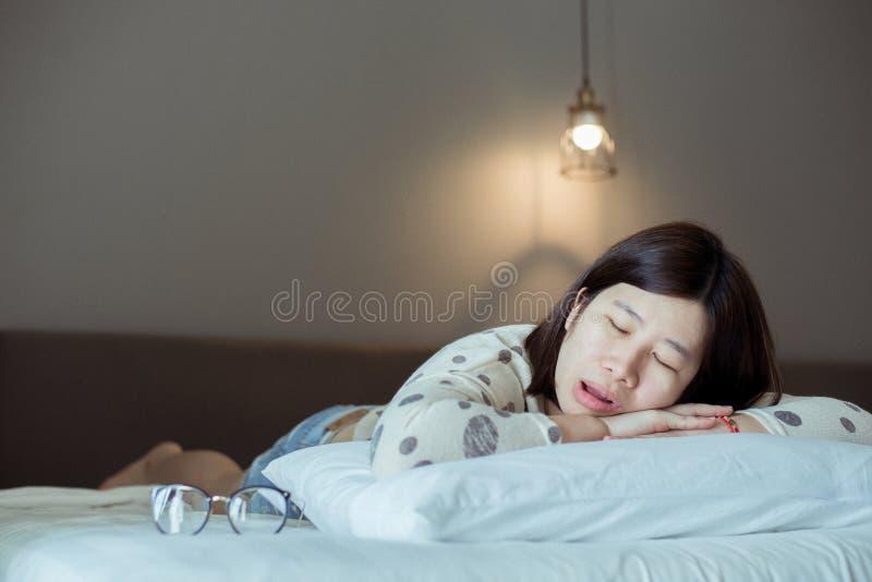 Mulheres asiáticas que ressonam porque devido ao snor cansado, fêmea ao dormir para abrir sua boca no quarto imagem de stock royalty free