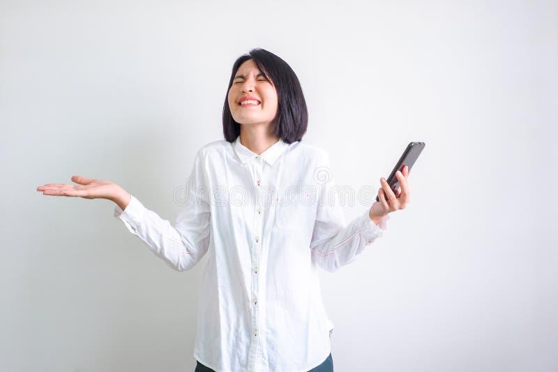 Mulheres asiáticas que vestem a camisa branca, telefone celular imagens de stock royalty free