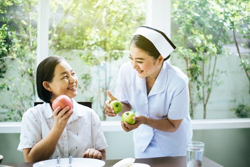 Mulheres asiáticas sêniores dão as mãos de fruta fresca de maçã em casa,Enfermeira cuida,Conceito de alimentação saudável para id imagens de stock royalty free