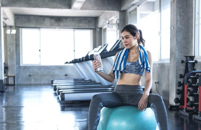 Mulheres asiáticas sedentas bebendo água após exercício na academia estilo de vida saudável fotografia de stock royalty free