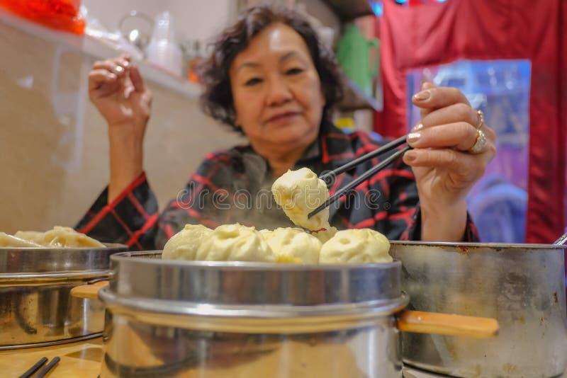 Mulheres asiáticas superiores de Defocus que comem bolos pequenos do vapor no restaurante chinês imagens de stock royalty free