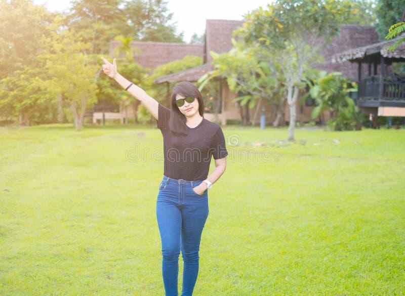 Mulheres asi?ticas bonitas ?culos de sol vestindo As poses estando levantam as mãos acima em um bom humor foto de stock