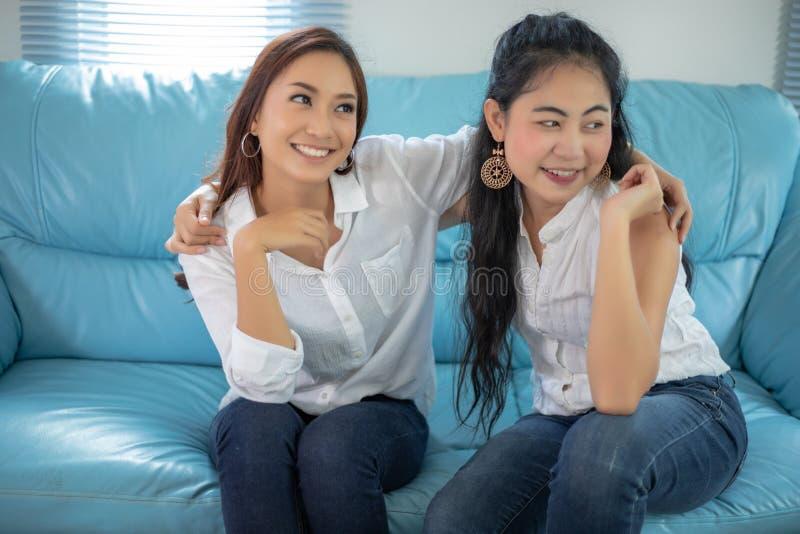 Mulheres asi?ticas do retrato do estilo de vida dos melhores amigos - sorriso feliz no sof? na sala de visitas imagem de stock royalty free