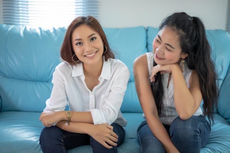 Mulheres asi?ticas do retrato do estilo de vida dos melhores amigos - sorriso feliz no sof? na sala de visitas imagens de stock royalty free