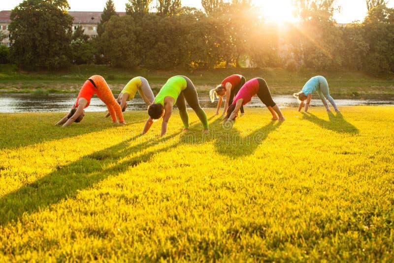 Mulheres ativas que praticam a ioga fora fotos de stock royalty free