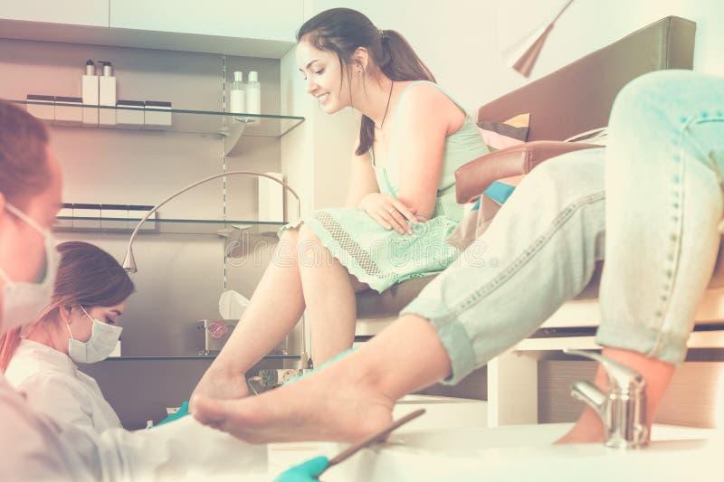 Mulheres atrativas que obtêm o pedicure pelo profissional no salo da beleza fotos de stock