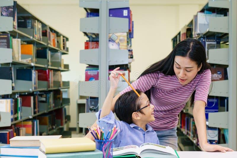 Mulheres bonitas com o livro de leitura do rapaz pequeno junto na biblioteca fotografia de stock