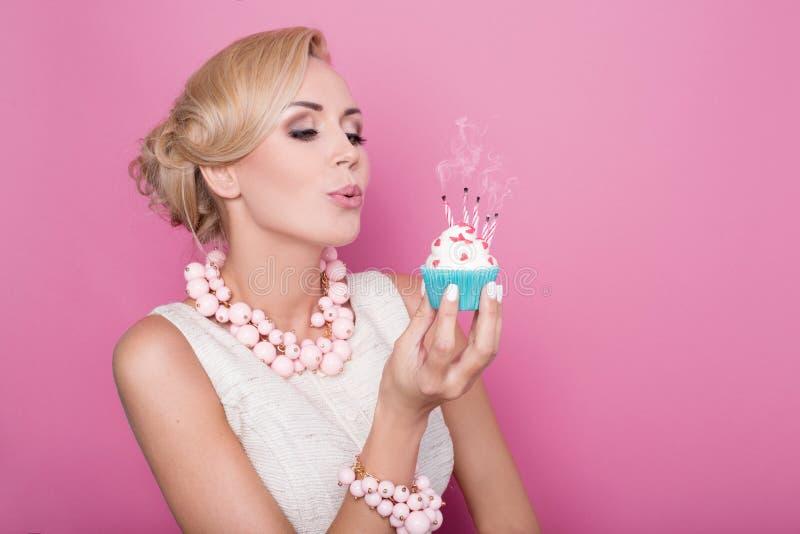 Mulheres bonitas com o vestido de creme que guarda o bolo pequeno com vela colorida Aniversário, feriado fotos de stock