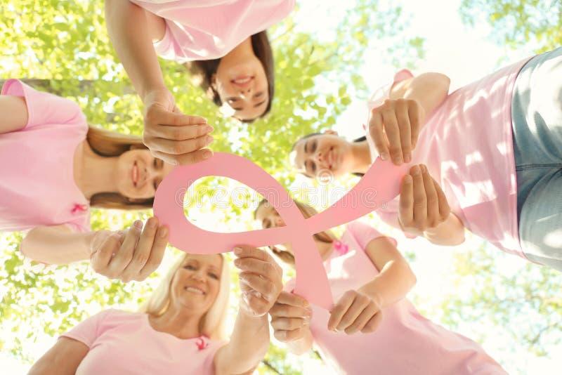 Mulheres bonitas das idades diferentes que guardam a fita de papel cor-de-rosa fora Conceito do cancro da mama fotos de stock