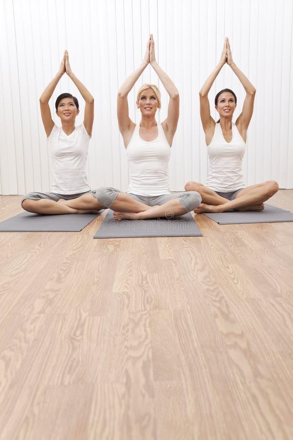 Mulheres bonitas do grupo inter-racial na posição da ioga imagem de stock