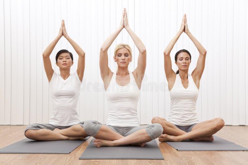 Mulheres bonitas do grupo inter-racial na posição da ioga foto de stock